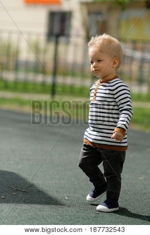 Portrait of toddler child outdoors. One year old baby boy at playground