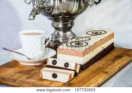 Gorgeous holiday cake Three-colate. Professional bakery. Three-layered chocolate cake decorated with chocolate patterns. The background is shiny samovar and porcelain cup with tea