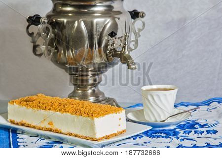 Gorgeous white cheesecake, sprinkled with sweet crumbs. Professional bakery. The background is a  samovar and porcelain cup with hot tea on blue kitchen towel