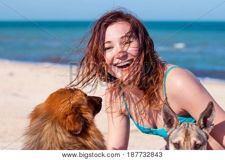 Beautiful girl with two dogs. Happy girl laughing and hugging dogs on the beach. A young woman smiles and hugs two stray dogs.