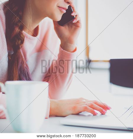 Young woman sits at the kitchen table using a laptop and talking on a cell phone