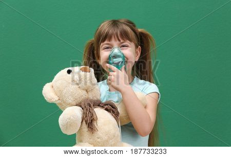 Cute little girl holding nebulizer and toy bear on color background. Allergy concept