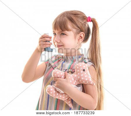 Cute little girl holding toy and inhaler on white background. Allergy concept