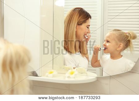 Cute little girl with her mother brushing teeth near mirror in bathroom