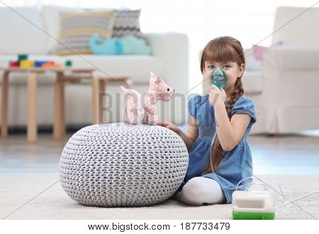Cute little girl using asthma nebulizer at home. Allergy concept