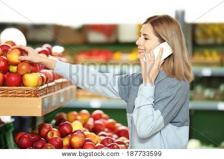 Beautiful woman buying fruits in market