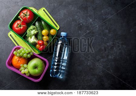 Lunch box with vegetable and fruits on stone table. Top view with copy space