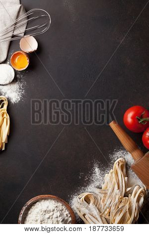 Pasta cooking ingredients on wooden kitchen table. Top view with space for your text