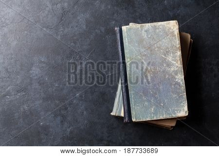 Old books on stone table. Top view with space for your text