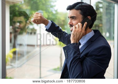 Businessman talking on mobile phone while looking through the window in conference centre