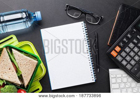 Office desk with supplies and lunch box with vegetables and sandwich. Top view with notepad for your text