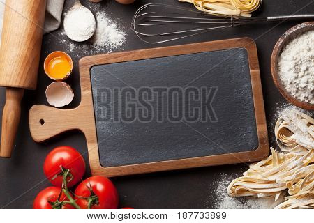 Pasta cooking ingredients on wooden kitchen table. Top view with chalkboard for your recipe