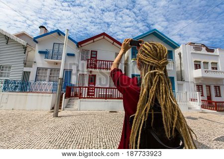 Striped houses in Costa Nova, Portugal. Young woman with blond dreadlocks makes a photo on a smartphone.