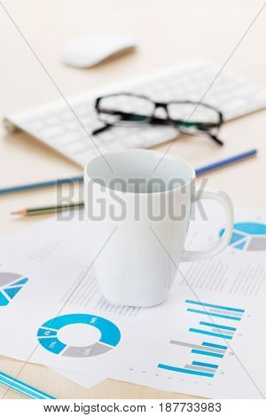Office workplace with supplies and reports on wood desk table