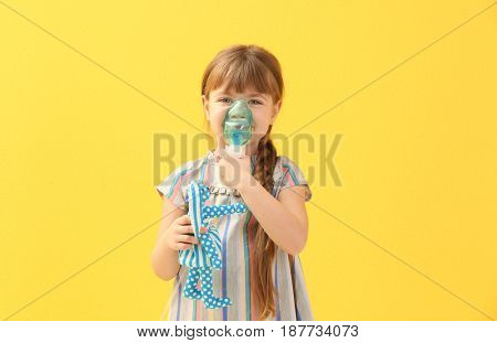 Cute little girl holding nebulizer and toy on color background. Allergy concept