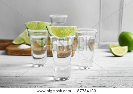 Tequila shots with juicy lime slices and salt on white wooden table