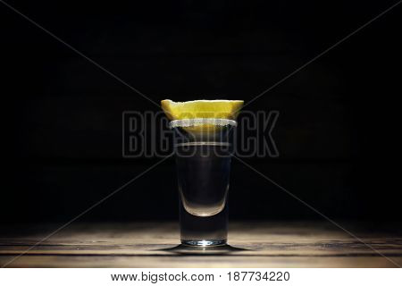 Tequila shot with juicy lemon slice and salt on dark background