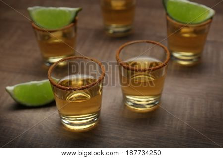 Golden tequila shots with lime on wooden background
