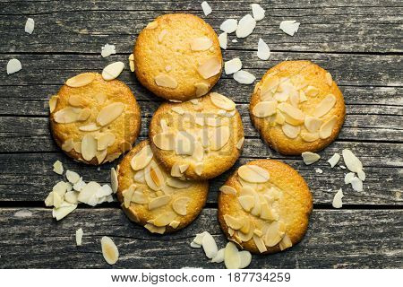 Sweet almond cookies on old wooden table. Black background. Top view.