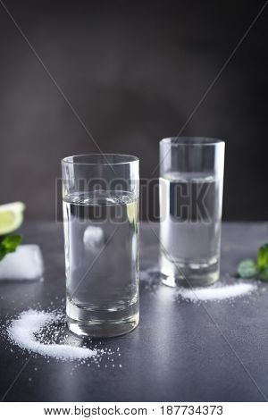 Tequila shots with salt on grey background