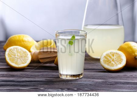 Lemon juice in glass and pitcher on wooden table