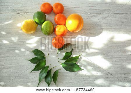 Appetizing fresh citrus fruits on white wooden background