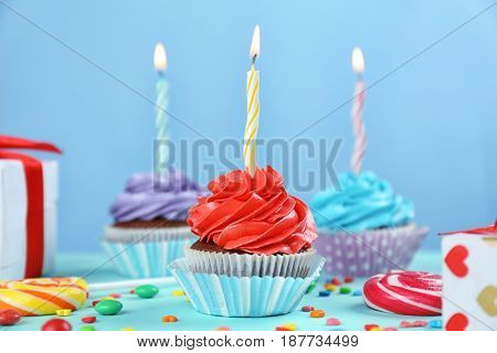 Tasty cupcake with candle on colorful background