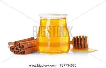 Cinnamon sticks and honey in jar isolated on white