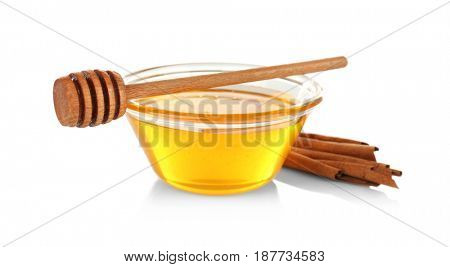 Cinnamon sticks and honey in glass bowl isolated on white