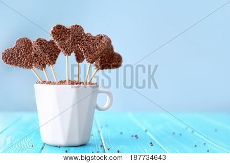 Heart shaped crispy dessert in cup on wooden table