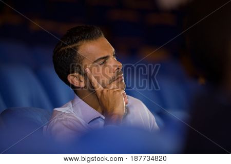 Thoughtful executive listening to speech at conference center