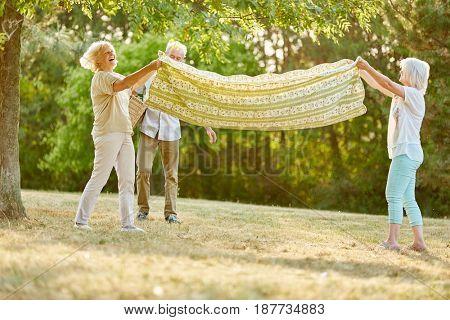 Group of seniors prepare blanket for picninc in summer