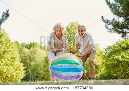 Senior couple playing and smiling happily with a ball in summer