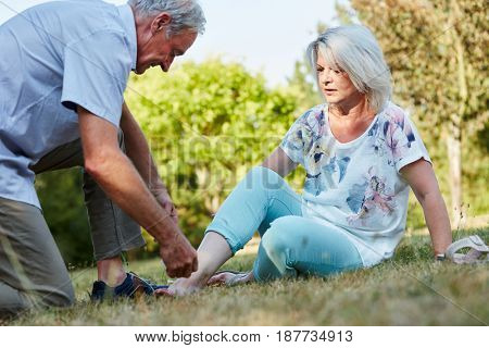 Old man helps woman with sprained ankle in the nature
