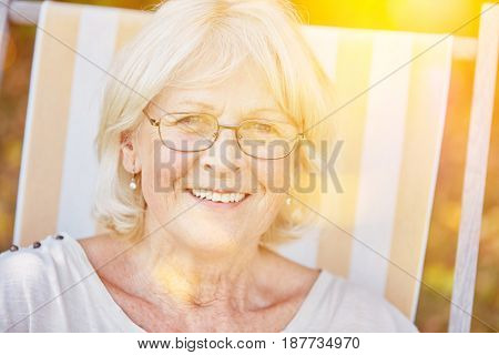 Happy senior woman wearing glasses and sitting on a deck chair in summer