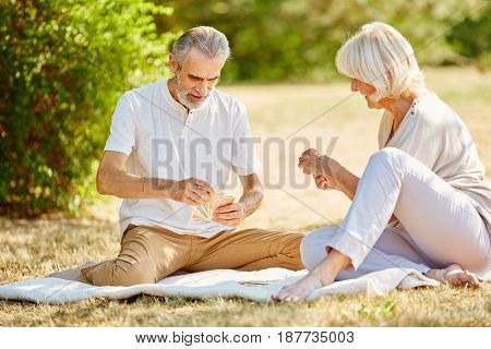 Senior couple playing a card game competition in the garden in summer