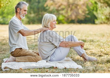 Old man gives a neck massage to his wife in summer in the garden