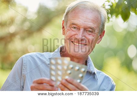 Senior man with medicament in his hands laughing in summer
