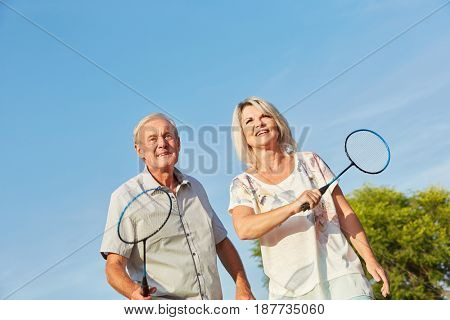 Happy senior citizens playing badminton as a team in summer