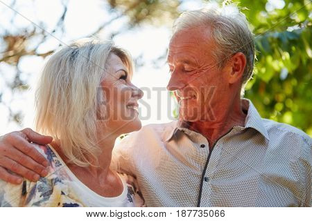 Happy senior couple in love hugs each other in summer