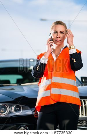 Woman with car breakdown calling towing company with phone