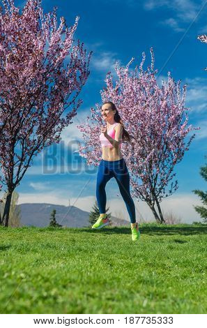 Woman in spring running or jogging as sport in spring