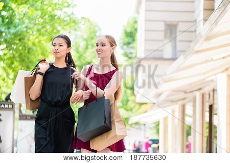 Two stylish young ladies out shopping standing in the street with their bags chatting and pointing