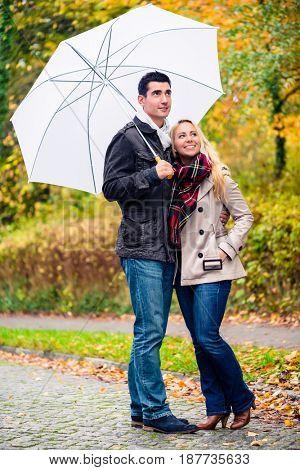 Couple enjoying fall day having walk despite the rain with umbrella