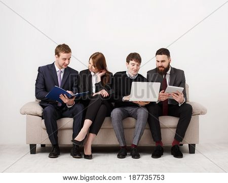 Business people teamwork. Busy team row on couch, partners working together at laptops and tablets, crop