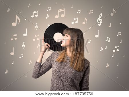 Young lady holding vinyl record on a brown background with musical notes behind her