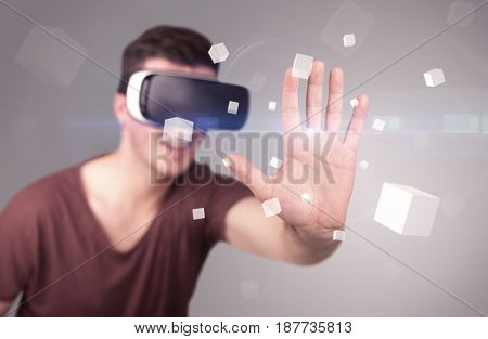 Young impressed man wearing virtual reality goggles with grey cubes around him