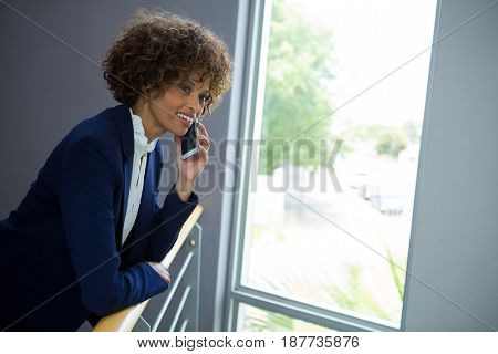 Businesswoman talking on mobile phone while leaning over the railing of staircase at conference centre