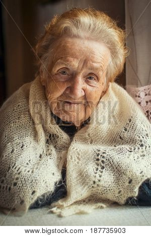 An elderly woman, a portrait sitting at the table. Russian or Ukrainian.