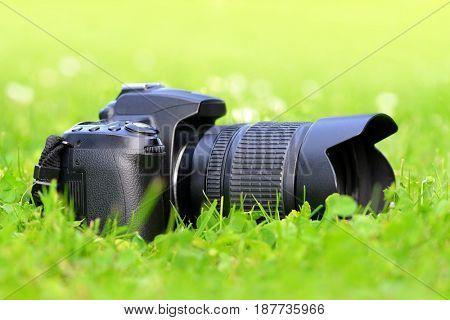 Digital photo camera on green grass.